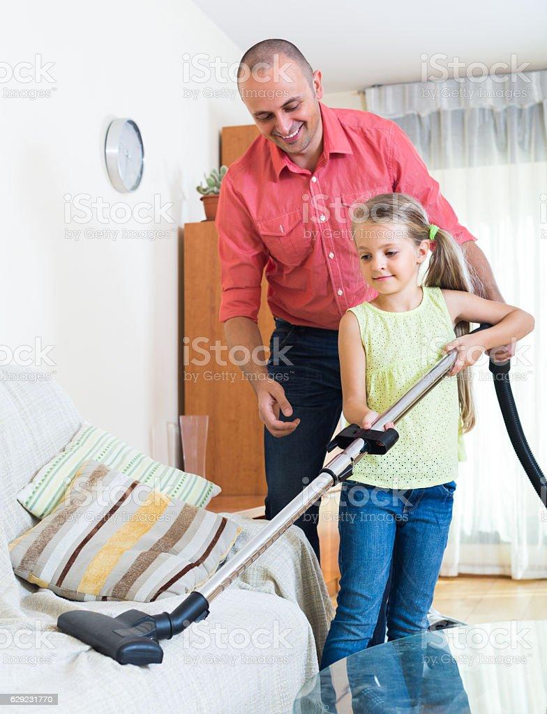 Homem e menina passar o aspirador em casa - foto de acervo
