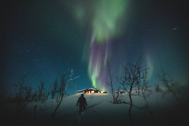 Man and Northern Lights over Riksgransen, Sweden stock photo