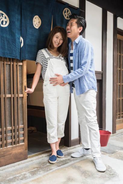 mann und schwangere frau stehen in tür, lächeln - latzhose für schwangere stock-fotos und bilder
