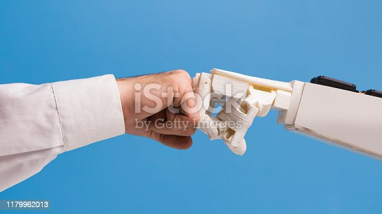 1050855372 istock photo Man and robot punching fists, successful coworking of human and ai 1179962013