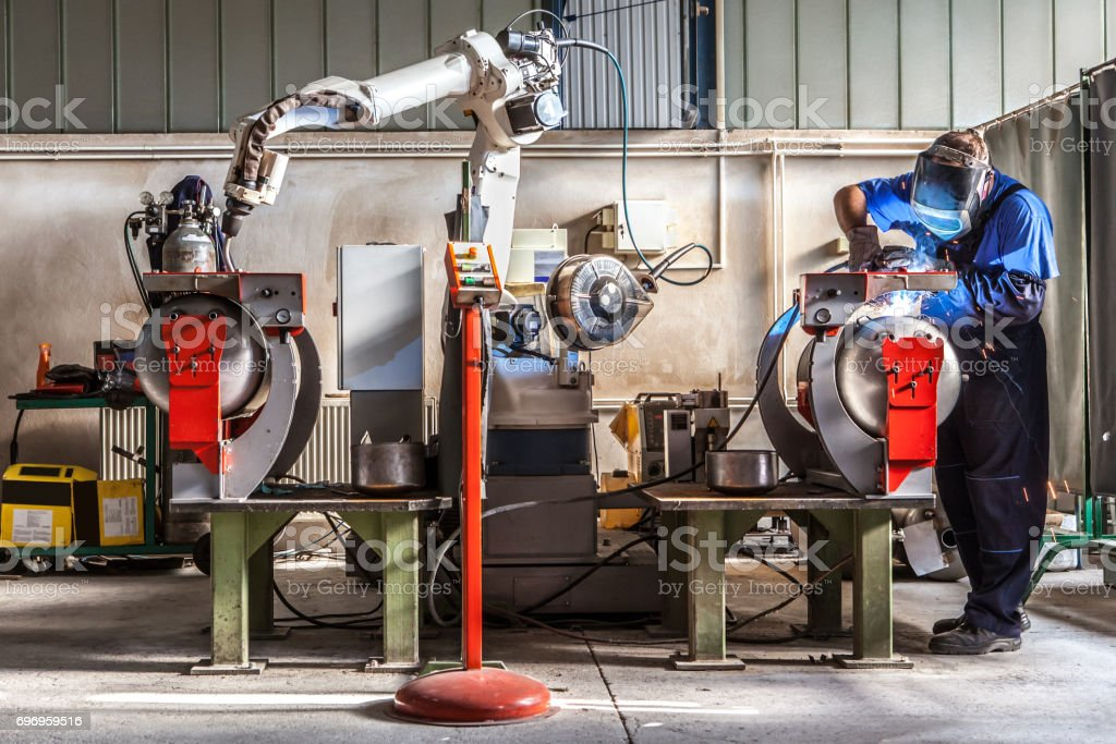 Man and robotic machine work together inside industrial building. The mechanical arm performs welds on metal components assisted by a worker who in turn manages welds manually. stock photo