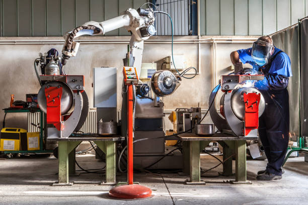 Man and robotic machine work together inside industrial building. The mechanical arm performs welds on metal components assisted by a worker who in turn manages welds manually. Details of the production process. metal worker stock pictures, royalty-free photos & images