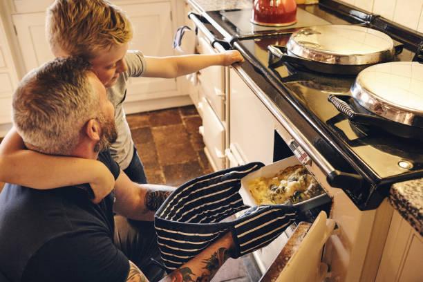 Hombre y su hijo poner verduras del tazón de fuente en el horno - foto de stock