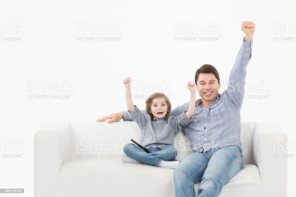 man and son watching sports on tv and supporting team stock photo