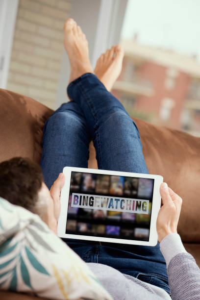 man and tablet with the text bingewatching in it stock photo