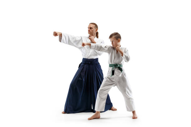 Man and teen boy fighting at aikido training in martial arts school stock photo