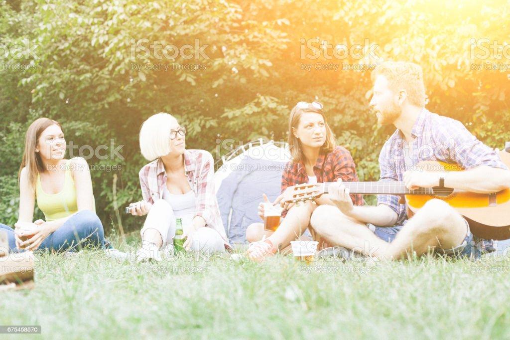 Homme et trois femmes sur le camping dans la nature photo libre de droits