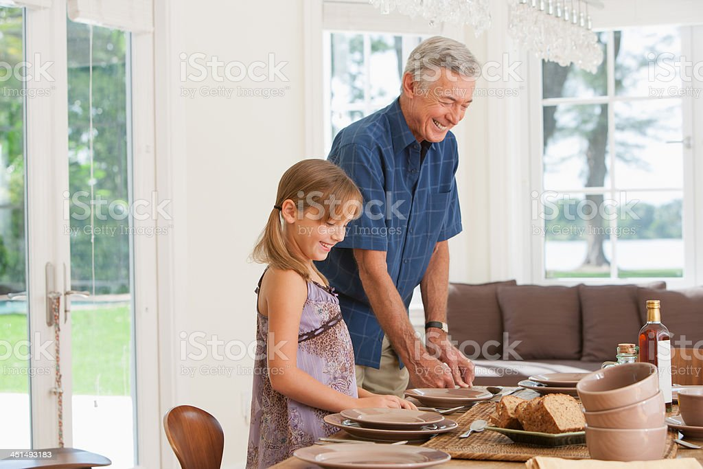 Man and two kids in dining room setting table royalty-free stock photo