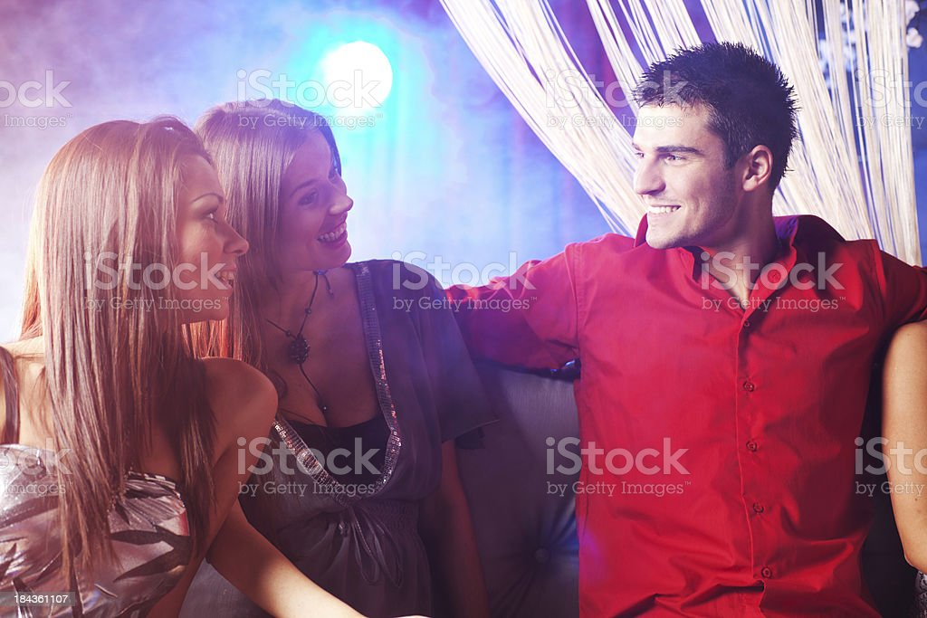 Man and two women talking at the disco royalty-free stock photo