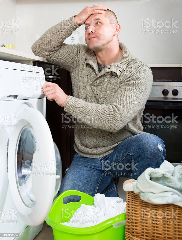 Man and washing machine stock photo