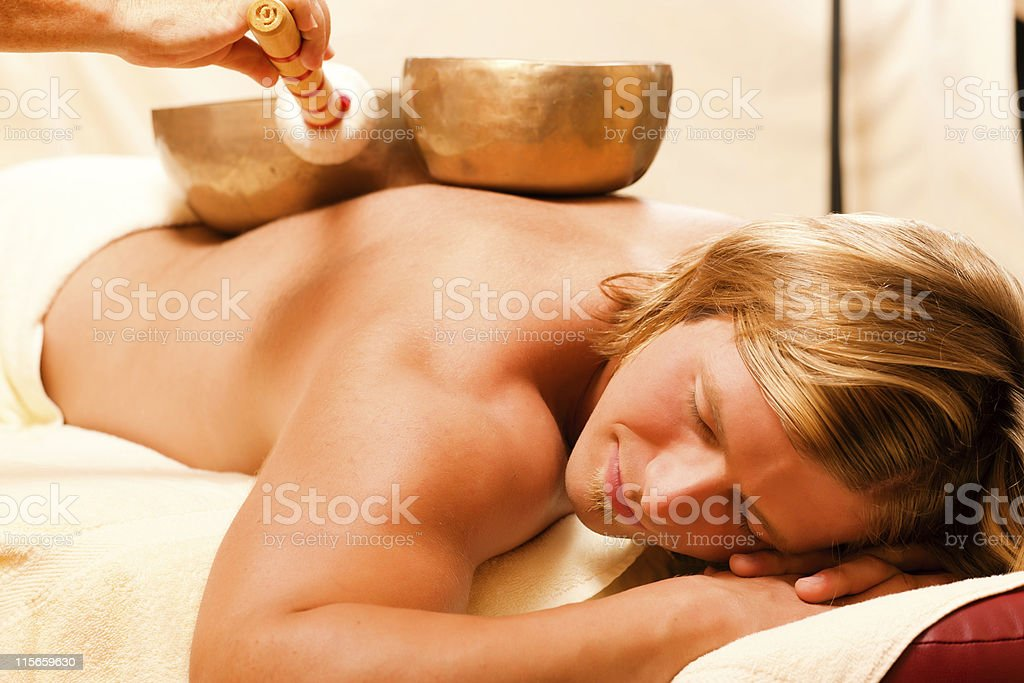 Man and Wellness with singing bowls stock photo