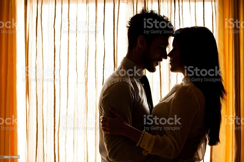 Hombre y mujer aproximadamente a kiss frente a la ventana - foto de stock