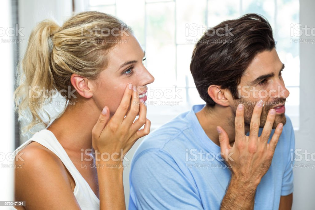 Man and woman applying moisturizer on their face stock photo
