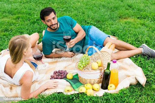 Man and woman are lying and relaxing with wineglasses on picnic outdoor.