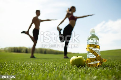 istock Man and woman are training in green park 989414990