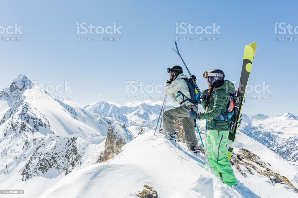 Man and woman at mountain summit during backcountry skiing day stock photo