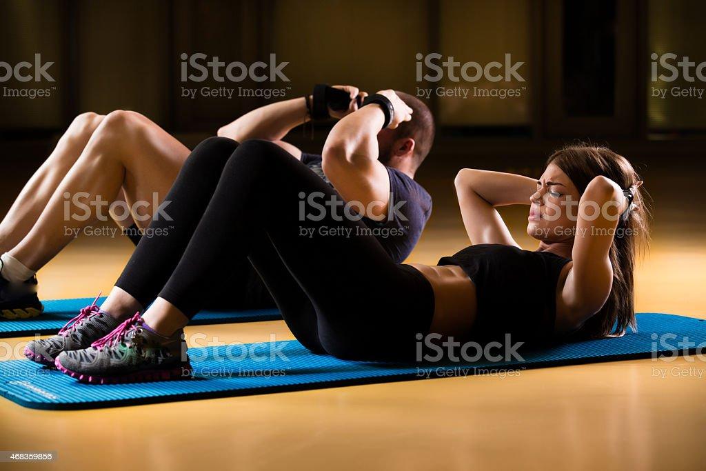 man and woman athletes performing sit ups on yoga mat royalty-free stock photo