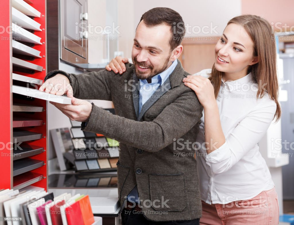 Man and woman choosing material for kitchen furniture stock photo