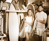 happy young man and woman choosing surfboards in the modern store