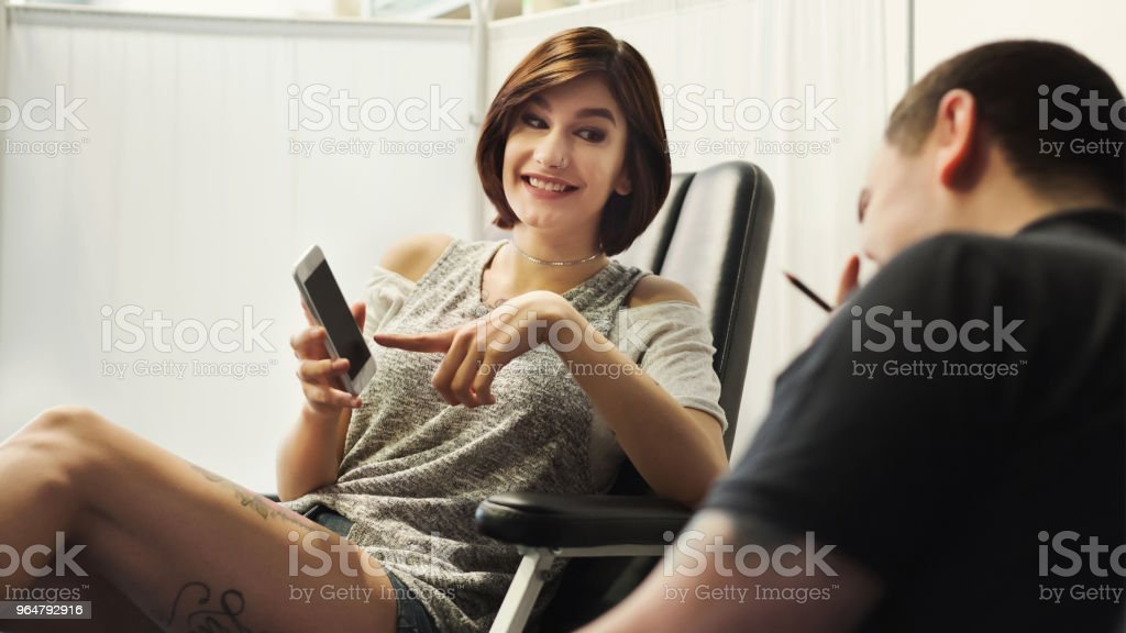 Man and woman choosing tattoo design in studio royalty-free stock photo