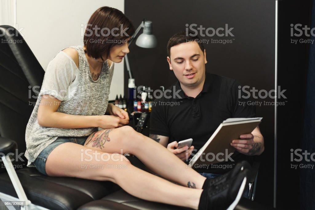 Man and woman choosing tattoo design in studio royalty-free stock photo