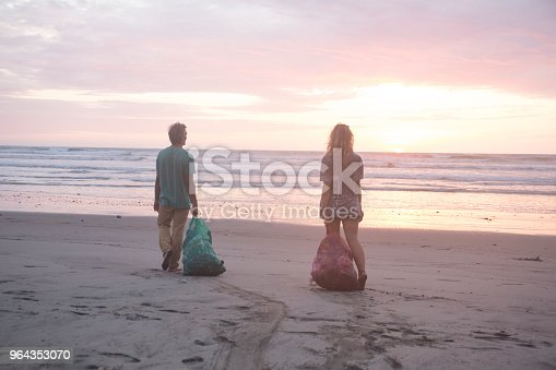 962184460 istock photo Man and woman clean garbage off of beach at sunset 964353070
