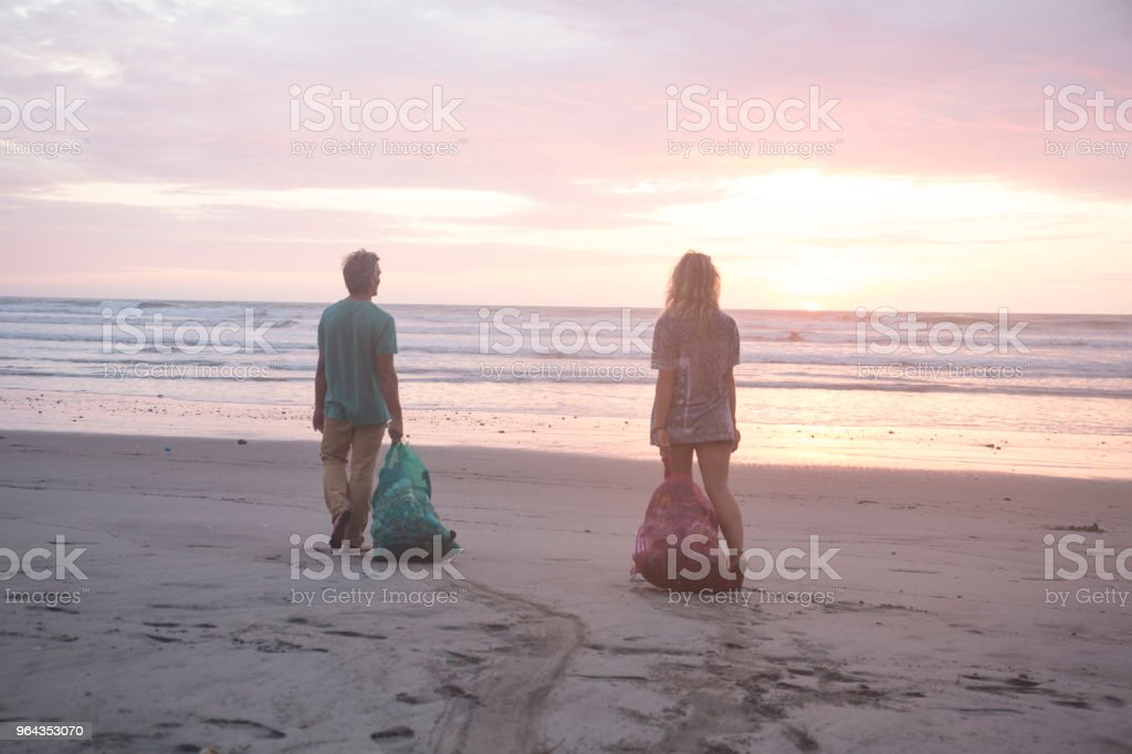Man and woman clean garbage off of beach at sunset stock photo