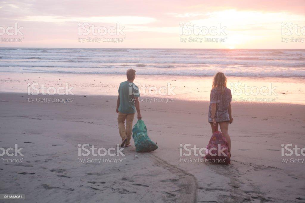 Homem e mulher limpam o lixo da praia ao pôr do sol - Foto de stock de 20-24 Anos royalty-free