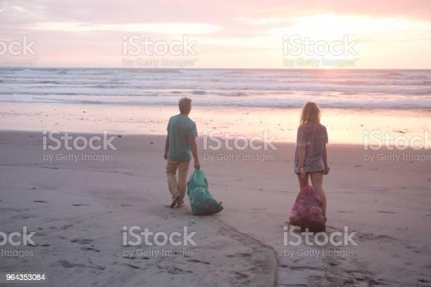 Foto de Homem E Mulher Limpam O Lixo Da Praia Ao Pôr Do Sol e mais fotos de stock de 20-24 Anos