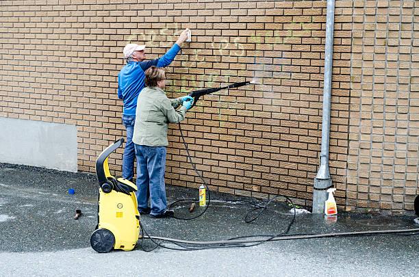 mann und frau reinigung graffiti auf ihre ziegelwand - heiratssprüche stock-fotos und bilder