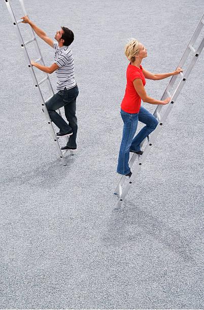 Man and woman climbing ladder outdoors stock photo