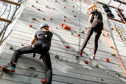 Well-equipped man and woman climbing the wall outdoors in the park for sports entertainment