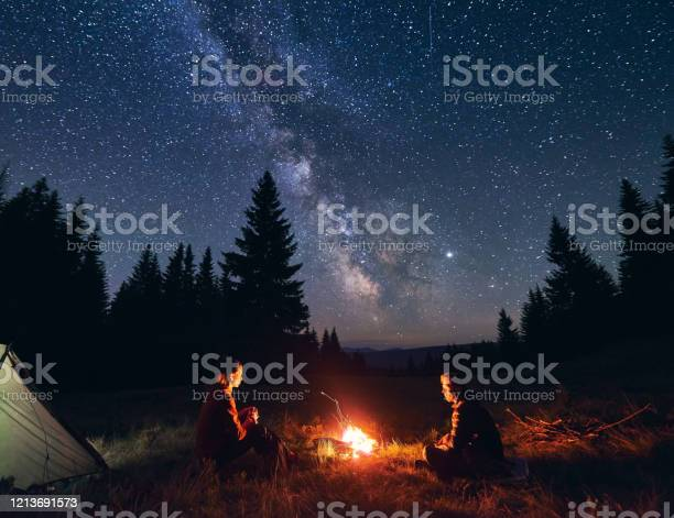 Photo of Man and woman communicate by fire against background of starry sky with bright Milky way. Night camping.
