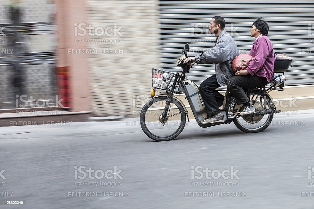 Man and woman commute on a scooter in China stock photo