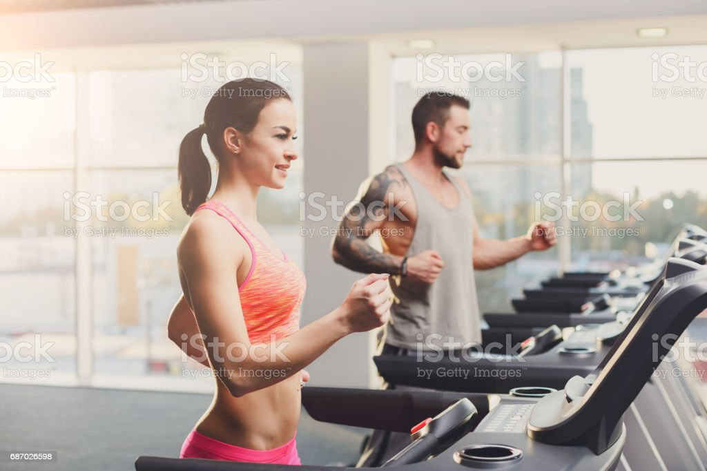 Man and woman, couple in gym on treadmills stock photo