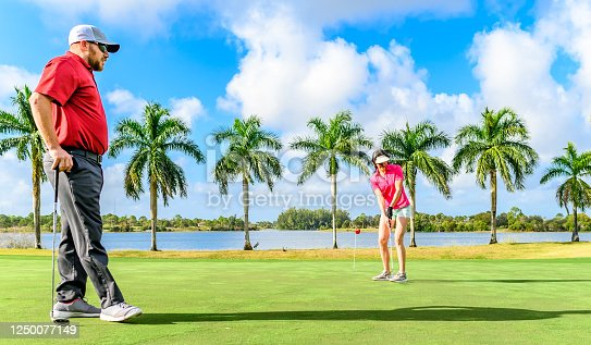 Beautiful young couple male and female play golf on a course lined with tropical palm trees on a sunny idyllic day