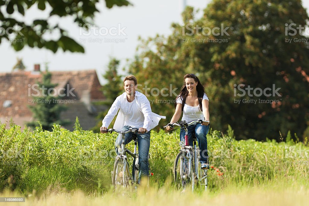 Man and woman cycling in summer royalty-free stock photo