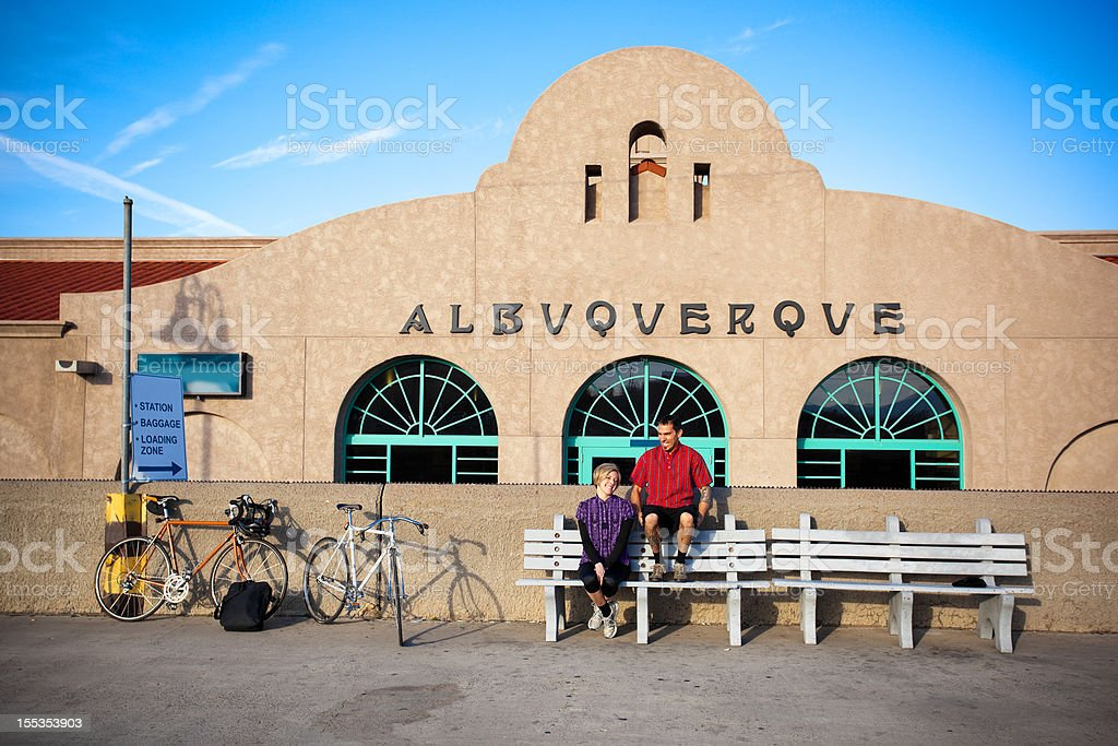 man and woman cyclist sitting at the train station stock photo
