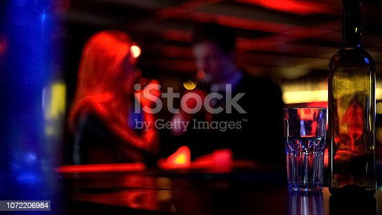 istock Man and woman dating in nightclub, both drinking beverages, blurred background 1072206984