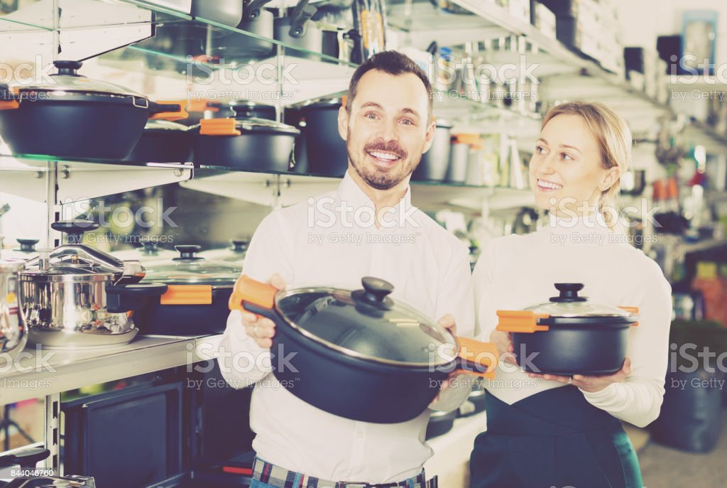 Man and woman demonstrate saucepans stock photo