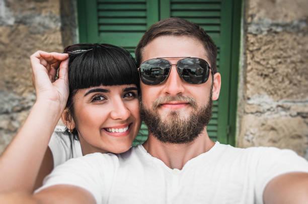 mann und frau machen ein selfie. mann und frau ruht im resort. ein verliebtes paar reist. hochzeitsreise. hochzeitsreise. foto am telefon. hochzeitsreise. liebes paar - hochzeitsreise amsterdam stock-fotos und bilder