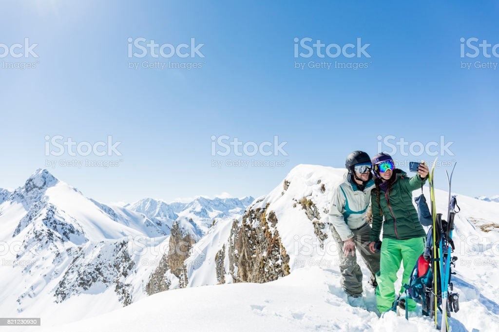 Man and woman doing a selfie photograph at mountain top during backcountry skiing day stock photo