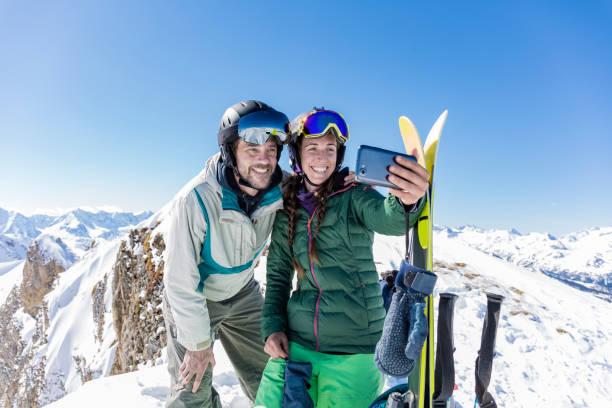 mann und frau tut ein selfie foto am berggipfel im backcountry-ski-tag - steuerungstechnik stock-fotos und bilder
