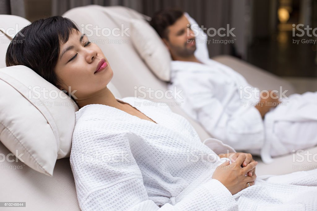 Man and woman dozing on deckchairs in spa salon stock photo