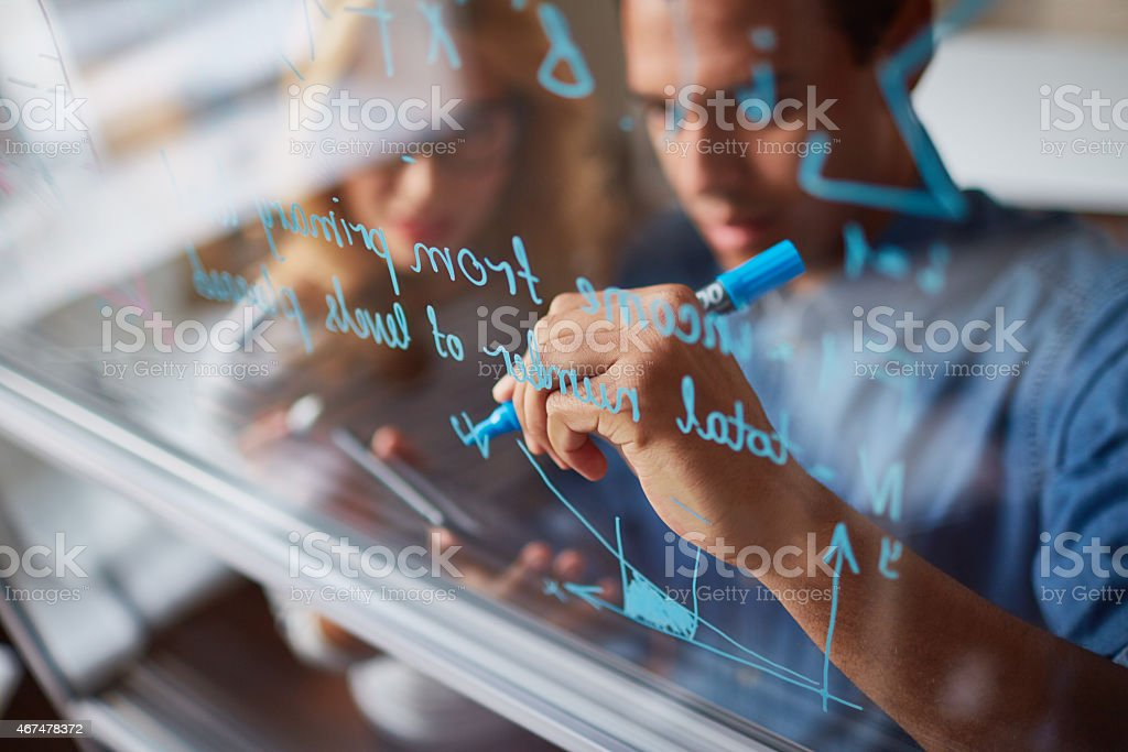 A man and woman draw a business plan on a glass window stock photo