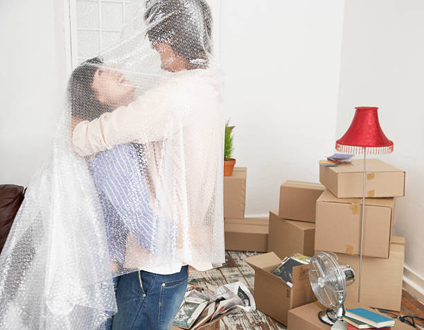 Man and woman embracing with bubble wrap in home with cardboard boxes stock photo