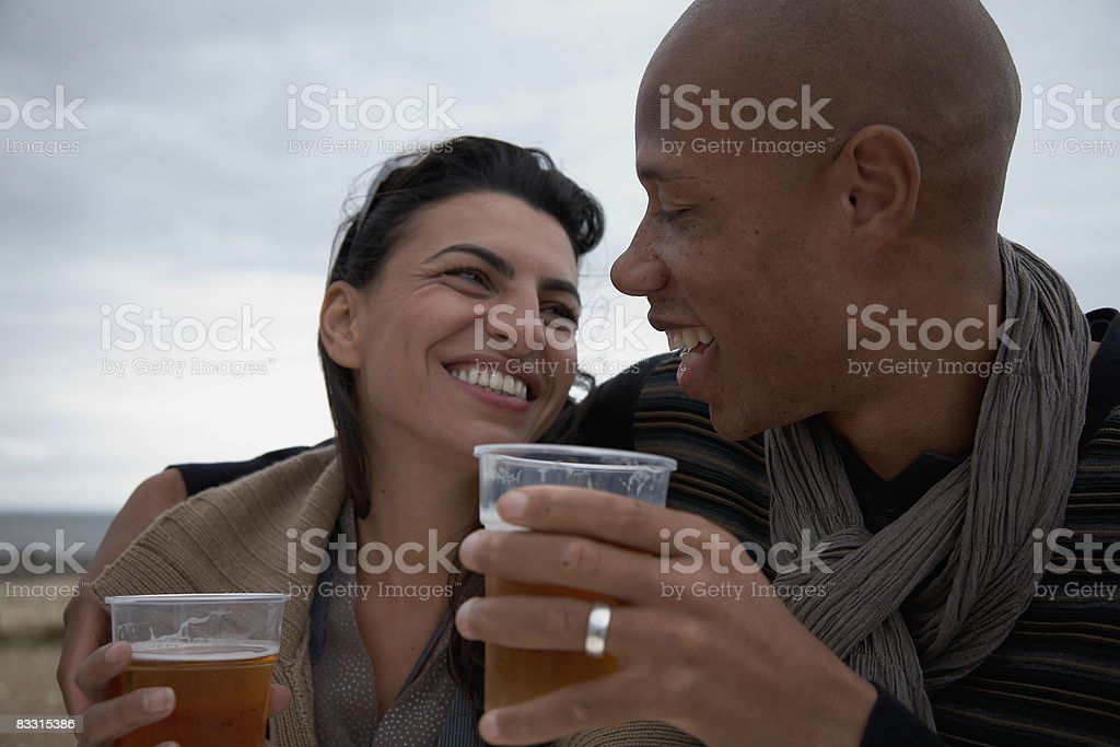man and woman enjoy a beer together foto stock royalty-free