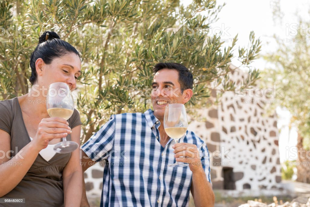 A man and woman enjoying a glass of wine stock photo