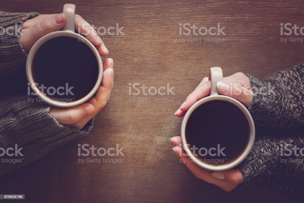 Man and woman enjoying coffee and lovely conversations in the romantic evening atmosphere. Hands warming with cups of coffee. royalty-free stock photo