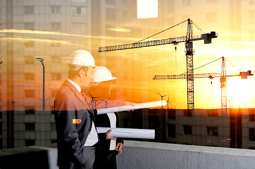 Man and woman examining architecture project, reflection of construction site on window, double exposure